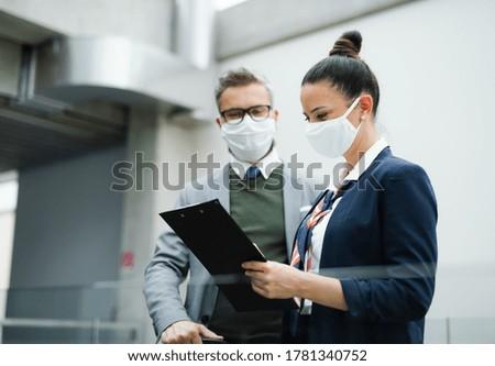 Flight attendant talking to mature businessman on airport, wearing face masks. Photo stock ©