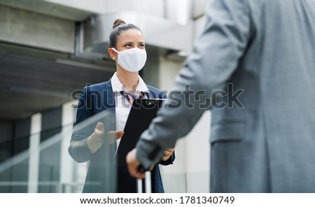 Flight attendant talking to unrecognizable businessman on airport, wearing face masks. Photo stock ©