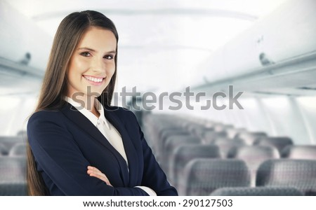 Flight attendant waiting for the passengers to board - Shutterstock ID 290127503