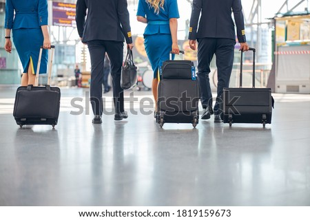 Flight attendants and pilots with trolley luggage bags walking in airport terminal Photo stock ©
