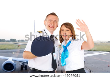 Flight crew. Cheerful pilot with hat in hand and flight attendant waving wearing uniforms with airliner standing at the airport.