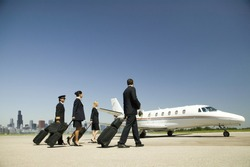 Flight crew wheeling suitcases to airplane on tarmac