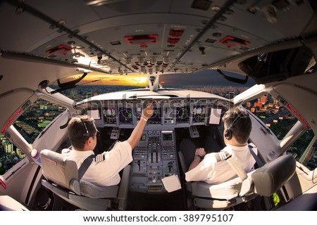 Flight Deck of modern aircraft. Pilots at work. Sunset view from the plane cockpit. #389795107