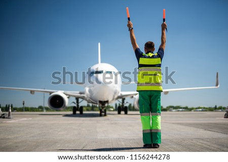 Flight is over. Back view of airport worker meeting passengers and directing the plane. Blue sky, aircraft and runway on background