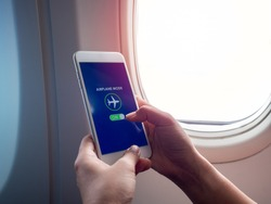 Flight mode concept. Finger sliding on screen for turned on airplane mode near the window on the airplane with copy space.