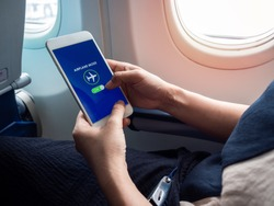 Flight mode concept. Hand holding white smartphone and turned on airplane mode on screen near the window on the airplane.