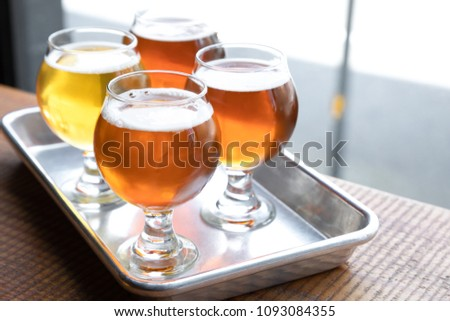 Flight of four craft beers in tulip glasses, on a metal sampling tray, at a local brewery, with space for text on the right