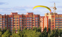 Flight of  motor paraplan.   man flies on  bright colorful motoparaplane above the village, field and construction site.