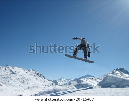 Flight on a snowboard on a background of snow mountains