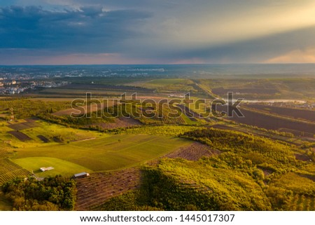 Flight over cultivating field in the spring at sunset.