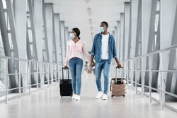 Flight Resumption. Black Couple Wearing Protective Masks Walking With Suitcases At Airport Terminal, Ready For Post-Quarantine Flight, Copy Space