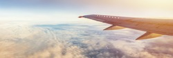 Flight wing panorama with copy space. Aircraft wing above the earth and clouds. Flight in sky. Travel by airlines for vacations.