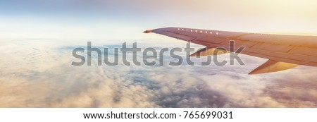 Flight wing panorama with copy space. Aircraft wing above the earth and clouds. Flight in sky. Travel by airlines for vacations. #765699031
