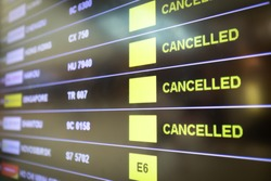 Flights cancelled and delayed on airport departure board due to covid-19 pandemic. Coronavirus causing disruption in air transport with airlines cancelling service. Travel and vacation cancellation