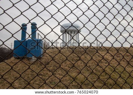 Flint Michigan Water Crisis. The Flint Michigan water tower seen through a chain link fence. This is a public structure and not a privately owned business or property.