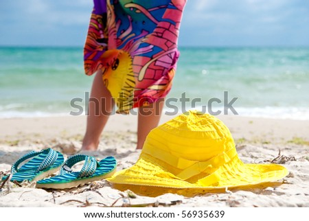 Flip-flop, hat and woman on the beach near sea. Focus on hat and flip-flops