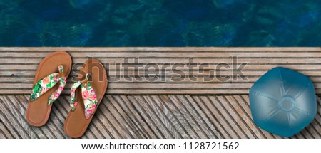 d71187abcc6 Flip Flops and a water ball placed on wooden planks at the side of a  swimming