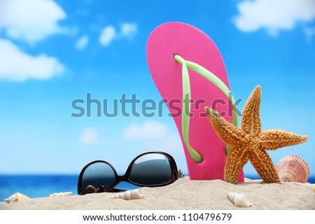 Flip-flops and sunglasses on sand beach.