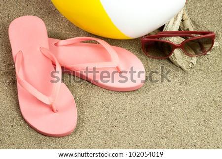 Flip Flops, beach ball and sunglasses on the beach