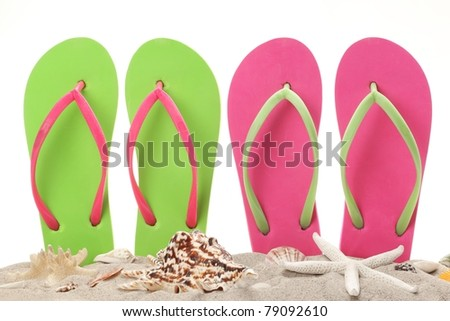 Flip Flops in the sand with shells. Summertime on beach concept.