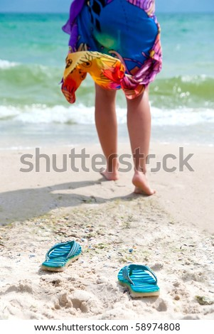 Flip-flops on beach and woman's leg going to the sea. Focus on flip-flops