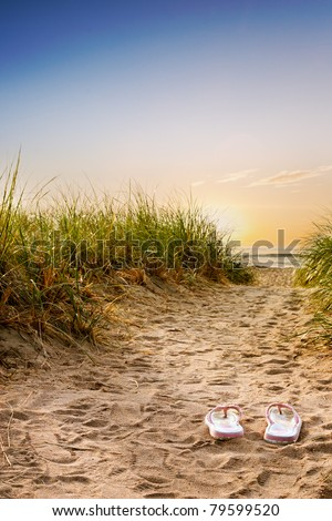 Flip flops on the sandy boardwalk over the dunes - stock photo