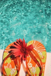 Flip Flops on white towel by swimming pool