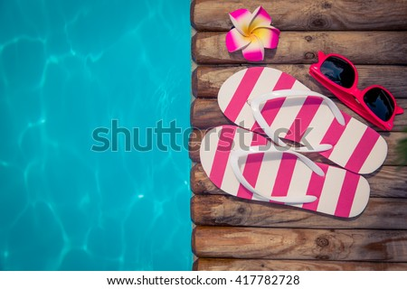 Flip-flops on wood against blue water background. Summer holiday concept