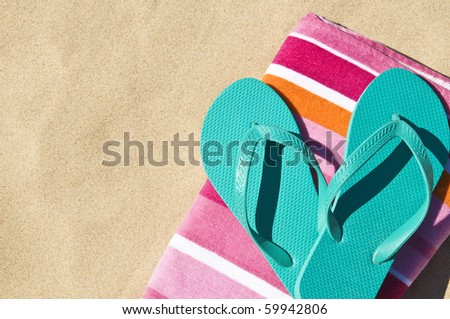 Flip-flops/Thongs and towel on white sand. - stock photo
