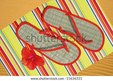 Flipflop sandals on mat by hibiscus flower on sand