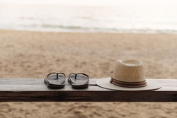 flipflops and straw hat place on the wooden chair at the beach