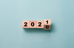Flipping of wooden cubes block to change 2020 to 2021 year. Merry Christmas and happy new year concept.