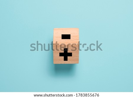 Photo of  Flipping wooden cube block to change minus sign to plus sign on blue background. Positive thinking and mindset concept.