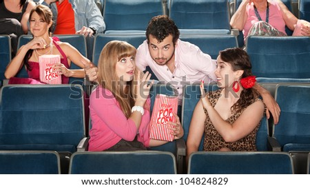 Flirtatious man with 2 young women in theater