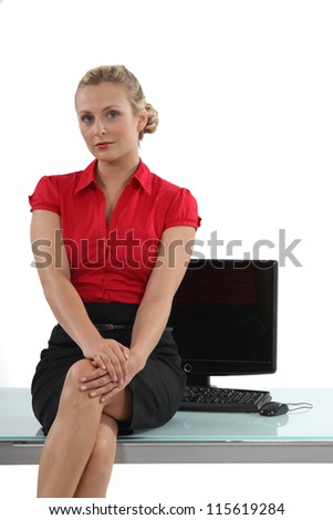 Flirtatious secretary sitting on the table