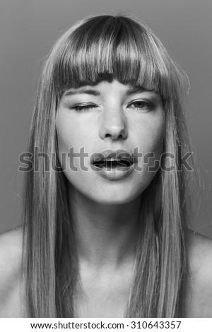 Flirting beautiful woman winking in black and white