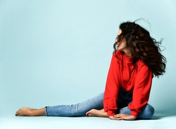 Flirting curly brunette adult woman in smoked blue glasses, red sweater and blue jeans jeggings is sitting posing on the floor looking aside at copy space over blue background