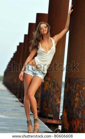 Flirting girl standing in a front of rusty background