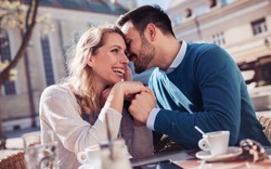 Flirting in a cafe. Beautiful loving couple sitting in a cafe enjoying in coffee and conversation. Love, romance, dating