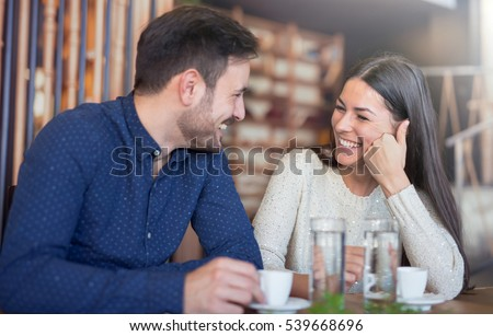 Photo of  Flirting in a cafe. Beautiful loving couple sitting in a cafe enjoying in coffee and conversation. Love and romance.