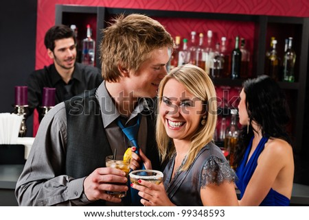 Flirting young happy friends enjoy drinks at cocktail bar