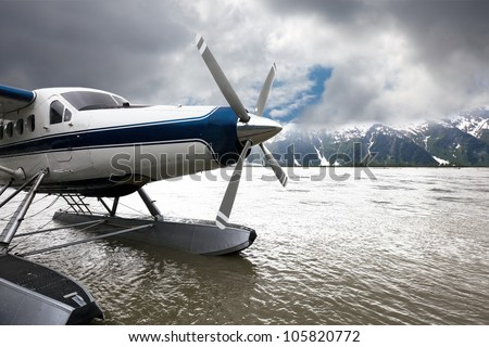 Float plane or seaplane in Alaska that has landed with storm clouds overhead.  The blue and white plane flew from Juneau.