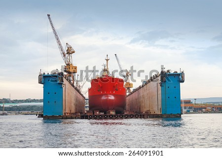 Floating blue dry dock with red tanker under repair inside, frontal view
