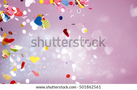Floating confetti of red, yellow, green and blue colors floating around in purple background with copy space #501862561