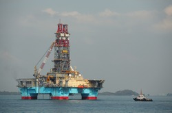 Floating drilling rig in the light of morning sun with attached tugboat