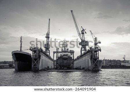Floating dry dock with old ship under repair inside, retro stylized black and white photo, front view
