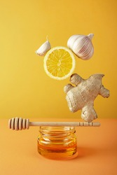Floating food balance equilibrium with set of ingredients for making drinks to support immune system and prevent diseases honey, ginger and lemon on yellow background. Alternative herbal medicine.
