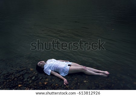 Floating girl lying on the rock of dark river . Ophelia conceptual #613812926