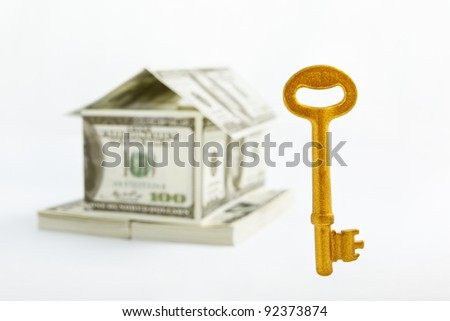Floating golden key in front of a house shape made from 100 dollar bills over white background
