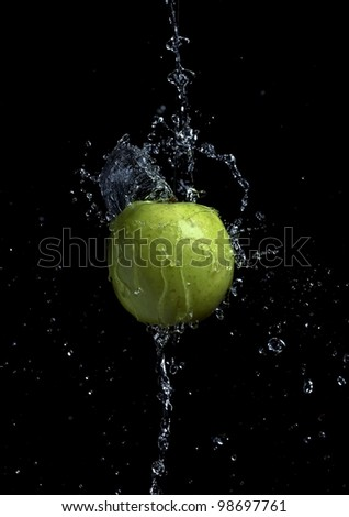 Floating green apple hit by water splash